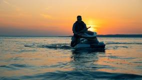 El jinete se incorpora en un esquí del jet en un fondo de la puesta del sol, cierre almacen de video
