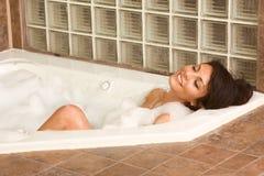 El joven atractivo gorges a la mujer que toma el baño de la espuma imagen de archivo libre de regalías