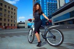 El joven delgado alegre se divierte a la mujer en la bicicleta Foto de archivo
