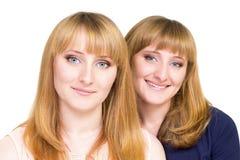 El joven hermana a las muchachas aisladas en el fondo blanco Foto de archivo