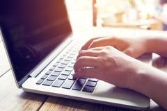 el ` joven hermoso s de la mujer del inconformista da el trabajo ocupado en su ordenador portátil que se sienta en la tabla de ma Fotografía de archivo