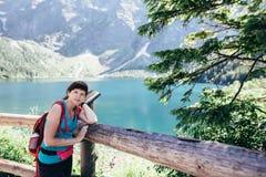 El joven se divierte a la muchacha que camina en un lugar pintoresco en el medio de las montañas cerca del lago Foto de archivo libre de regalías