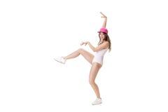 El joven se divierte la mujer en el mono blanco y el baile rosado del sombrero en el fondo blanco Imagen de archivo libre de regalías
