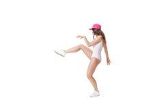 El joven se divierte la mujer en el mono blanco y el baile rosado del sombrero en el fondo blanco Fotos de archivo libres de regalías
