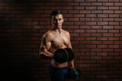 El joven se divierte los trenes del individuo el bíceps Imagen de archivo libre de regalías