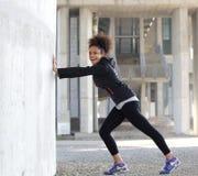 El joven sonriente se divierte a la mujer que estira ejercicio al aire libre Fotografía de archivo