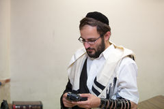 El judío ortodoxo limpia el lugar del tefillin después de rezos Fotos de archivo