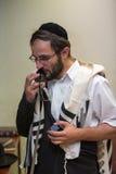 El judío ortodoxo limpia el lugar del tefillin después de rezos Imagenes de archivo