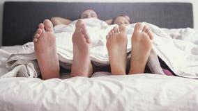 El juego alegre cariñoso joven de los pares y bailar sus pies bajo rato combinado despierta en cama por la mañana fotos de archivo