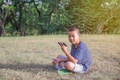 El juego asiático lindo feliz del juego del muchacho con smartphone se sienta en el parque Fotografía de archivo