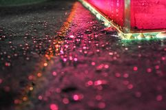 El juego asombroso de luces y de colores, el tanque de agua llenó de agua rosada puesta en la alfombra verde con muchas gotitas imagen de archivo libre de regalías