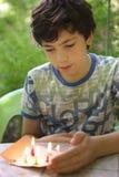 El juego dañoso del muchacho del adolescente con las velas quema el fuego Imagenes de archivo