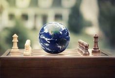 El juego de ajedrez figura el globo de la tierra en el fondo casero Fotos de archivo