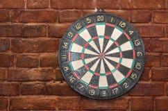 El juego de dardos, contra una pared de ladrillo vieja Imagenes de archivo