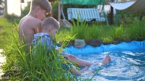 El juego de dos niños cerca de un pequeño lago, las flores y la hierba crecen alrededor del lago Los niños crean salpican del agu almacen de metraje de vídeo