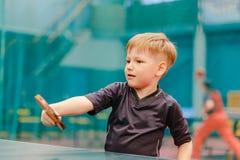 El juego de los tenis de mesa, el niño bate una pelota de tenis Imágenes de archivo libres de regalías