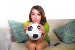 El juego de observación joven de la televisión de la mujer nerviosa y hermosa del fanático del fútbol que se sentaba en el sofá p fotos de archivo libres de regalías