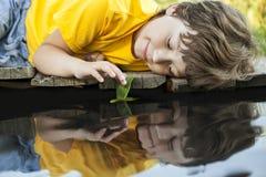 El juego del muchacho con la nave de la hoja del otoño en el agua, niños en parque juega w Imagenes de archivo