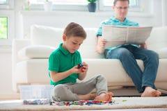 El juego del niño pequeño, padre leyó el periódico Fotografía de archivo libre de regalías