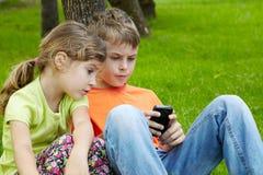 El juego electrónico del juego del muchacho, hermana se sienta al lado de él Imágenes de archivo libres de regalías