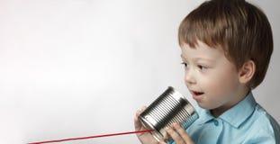 El juego feliz en el teléfono de la lata, muchacho del muchacho ató un teléfono a fotografía de archivo libre de regalías