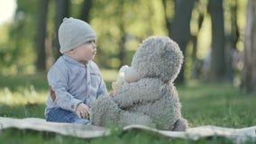 El juego lindo del niño con el peluche refiere una sobrecama en parque almacen de metraje de vídeo