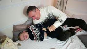 El juego que cosquillea, hijo juega con el papá, familia feliz, niño pasa tiempo con un buen padre, almacen de metraje de vídeo