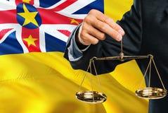 El juez está sosteniendo escalas de oro de la justicia con el fondo de la bandera de Niue que agita Tema de la igualdad y concept libre illustration
