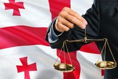 El juez georgiano está sosteniendo escalas de oro de la justicia con el fondo de la bandera de Georgia que agita Tema de la igual foto de archivo