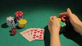 El jugador afortunado que muestra abajo de la mano de la escalera real, jugador de póker gana el banco en casino metrajes