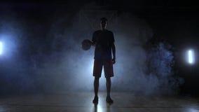 El jugador de básquet en pantalones cortos rojos de la ropa de deportes y una camiseta azul va en una cancha de básquet oscura en almacen de metraje de vídeo