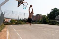 El jugador de básquet está alrededor a la clavada Foto de archivo libre de regalías