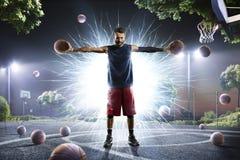 El jugador de básquet está celebrando dos bolas en sus manos Imagenes de archivo