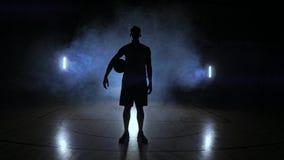 El jugador de básquet golpea la bola teniendo en cuenta las lámparas que brillan detrás de soportes en la Duma y golpea la bola e almacen de metraje de vídeo