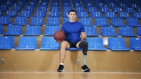 El jugador de básquet inhabilitado se sienta, deteniendo una bola, cierre almacen de video