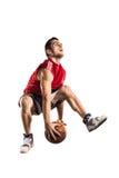 El jugador de básquet que salta y que gotea aislado Foto de archivo