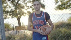 El jugador de básquet se coloca con la bola en la corte, esperando el juego en la c?mara lenta El mejor retrato del jugador metrajes
