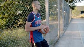 El jugador de básquet se coloca con la bola en la corte, esperando el juego en la c?mara lenta El mejor retrato del jugador almacen de metraje de vídeo