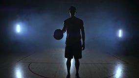 El jugador de básquet se coloca en un patio oscuro y celebra la bola en sus manos y miradas en la cámara en la oscuridad almacen de metraje de vídeo