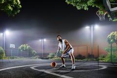 El jugador de básquet se está resolviendo en corte de noche Fotografía de archivo