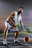 El jugador de básquet se está resolviendo en corte de noche Foto de archivo libre de regalías