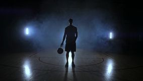 El jugador de básquet va a la cámara y golpea la bola en la tierra después para y celebra la bola que mira metrajes