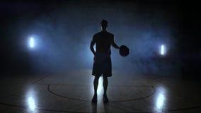 El jugador de básquet va a la cámara y golpea la bola en la tierra después para y celebra la bola que mira almacen de metraje de vídeo