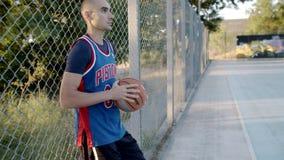 El jugador de básquet viene al patio para el juego El jugador de básquet está jugando en el amanecer del sol Ma?ana almacen de video