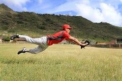 El jugador de béisbol se zambulle para coger la bola Imagen de archivo