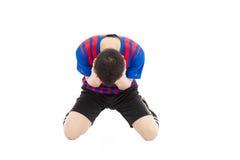 El jugador de fútbol agitated se arrodilla abajo y cubre su cara para llorar Imagen de archivo libre de regalías