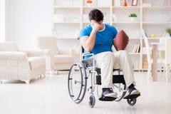 El jugador de fútbol americano del hombre joven que se recupera en la silla de ruedas Fotos de archivo