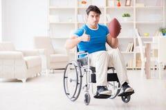 El jugador de fútbol americano del hombre joven que se recupera en la silla de ruedas Imagen de archivo libre de regalías