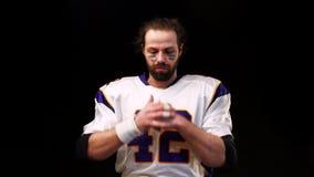 El jugador de fútbol americano endereza hacia fuera y estira sus brazos y los brazos antes del partido, dando la impresión de almacen de metraje de vídeo