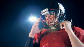 El jugador de fútbol americano pone el casco protector, cierre para arriba metrajes